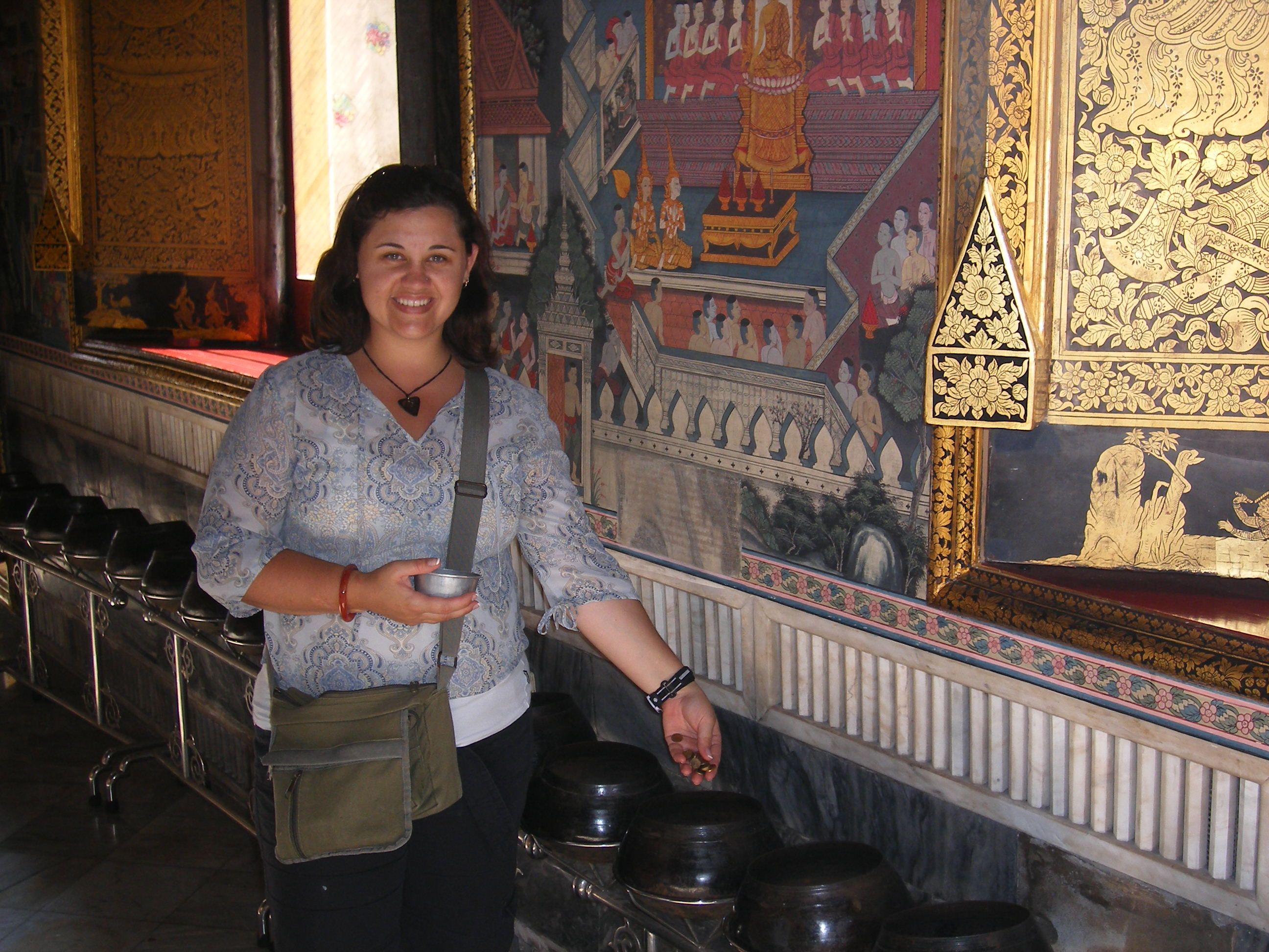Depositing lucky coins into the wishing pots at the reclining Buddha